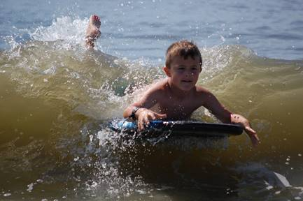boy on boogie board in ocean